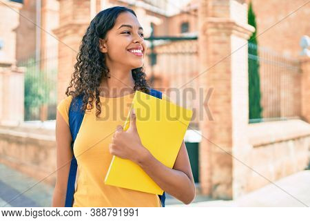 Young african american student girl smiling happy holding book at university campus.