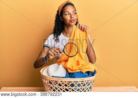 Young african american girl holding magnifying glass looking for stain at clothes smiling looking to the side and staring away thinking.