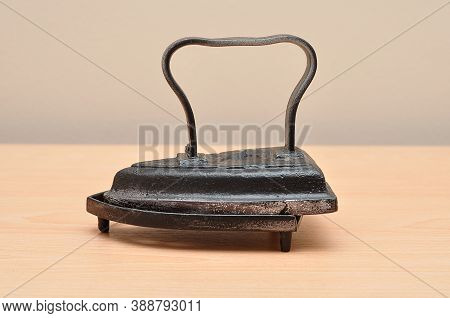An Antique Iron On A Table On A Stand