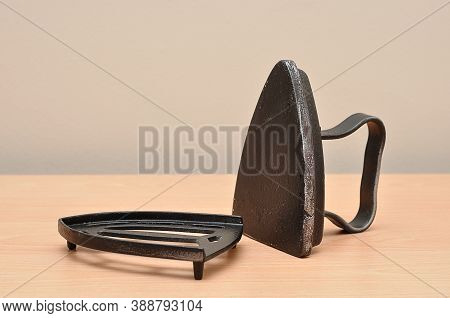 An Antique Iron On A Table With A Stand
