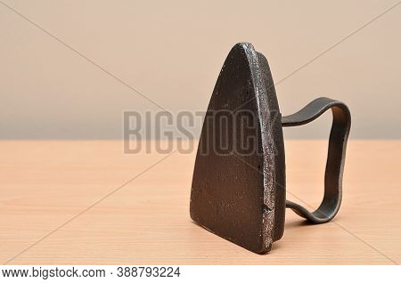 An Antique Iron Placed Up Right On A Table