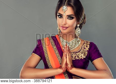 Portrait of a beautiful indian girl in a greetting pose to Namaste hands .India woman in traditional