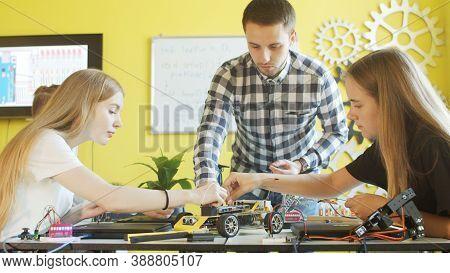 Unrecognizable Students Assembling Car In Robotics Class