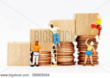 Miniature People With Coins Stack And Wooden Box.