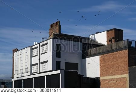 Doncaster,yorkshire, England - October 7, 2020. Black And White Building With Birds Flying Over.