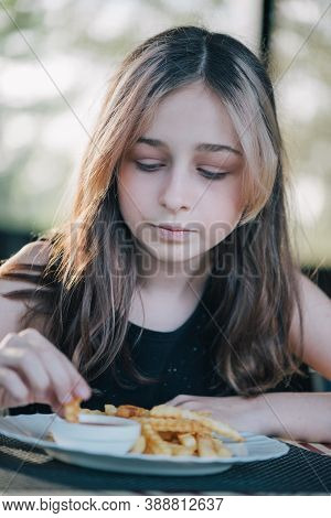 Happy Little Girl Eating A French Fries. Beautifullittle Girl Sitting At Table And Eating French Fri