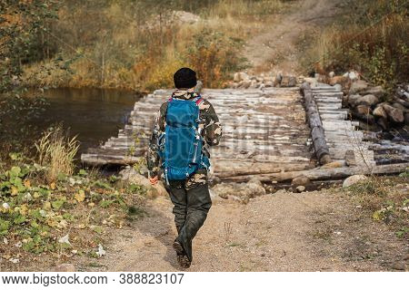Back View Photo Of Male Backpacker Walking On Forest Path And Viewing Landscape In Autumn Vacation