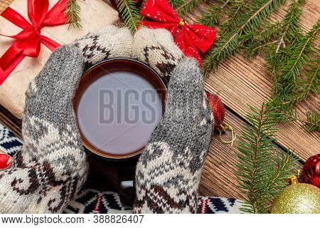 Hands In Mittens Holding Cup Of Tea Close Up On The Brown Brushed Wooden Fur Pine Branches Gift Toys