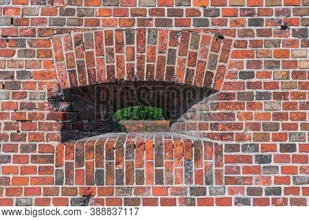 Medieval Brick Wall With Arched Embrasure. Texture Of Red Masonry. Part Of An Ancient Defensive Stru
