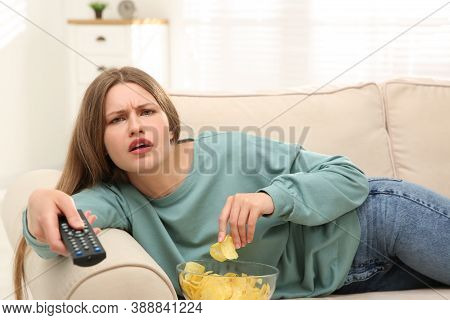 Lazy Young Woman With Bowl Of Chips Watching Tv On Sofa At Home