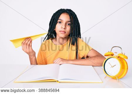 Young african american girl child with braids holding paper airplane while studying thinking attitude and sober expression looking self confident
