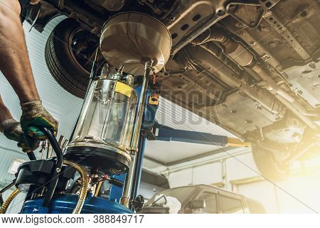 Changing Gear Oil Or Engine Or Motor Oil In Car Service With Auto On Lift, Maintenance Concept.
