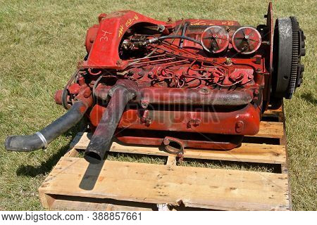 The Used Red Tractor Engine Left On A Pallet Is For Sale At A Farm Show Flea Market.