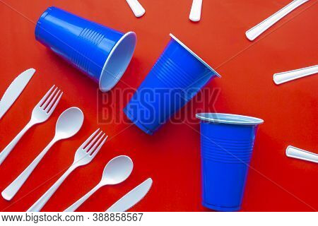Single Use White Plastic Cutlery And Blue Plastic Glass On A Red Background. Concept: Ban Single Use