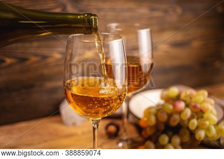 Bottle Of Dry White Wine With A Glass And A Bunch Of Grapes On A Wooden Table. Concept Of Viticultur