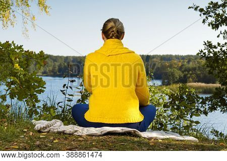 Beautiful Young Girl Meditating In Autumn Park. Woman Meditates In The Forest In Sunny Day.