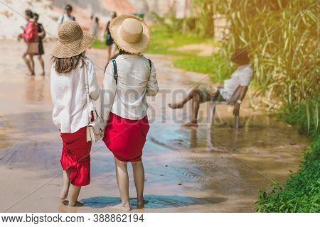 Back View Of Tourists Walk On Feet In The Red Stream ( It Also Named Fairy Stream) With Beautiful Sc