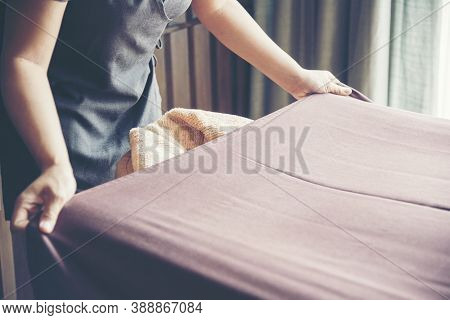 House Cleaner Prepare Bed Sheet In  Luxury Hotel. Chambermaid Housework Laundry Make Bed Sheet.
