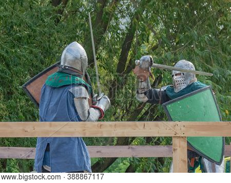 Two Knights On Foot In Heavy Medieval Armor Fight With Swords. They Are Protected By Iron Helmets An