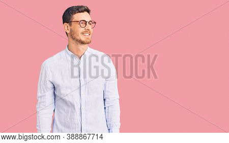 Handsome young man with bear wearing elegant business shirt and glasses looking away to side with smile on face, natural expression. laughing confident.
