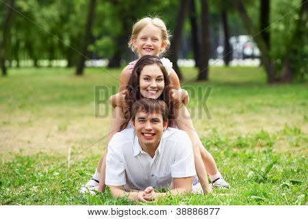 Young Family Outdoors on the grass in Park in summer
