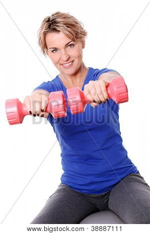 Cute mid aged women do exercises with dumbbells on a abs ball