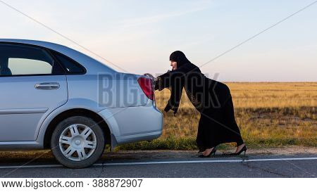 An Islamic Woman Is Pushing A Car Along The Road. Woman Driver Car Breakdown.