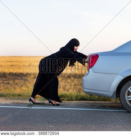 An Islamic Woman Is Pushing Car Along The Road. Woman Driver - Car Breakdown.