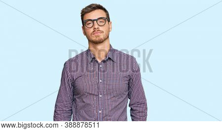 Handsome caucasian man wearing casual clothes and glasses relaxed with serious expression on face. simple and natural looking at the camera.