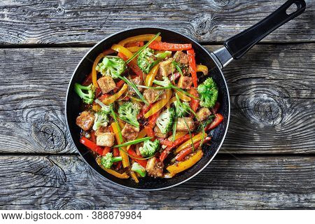 Kung Pao Tofu With Mixed Peppers, Broccoli And Scallions In A Skillet On A Rustic Wooden Table, Chin