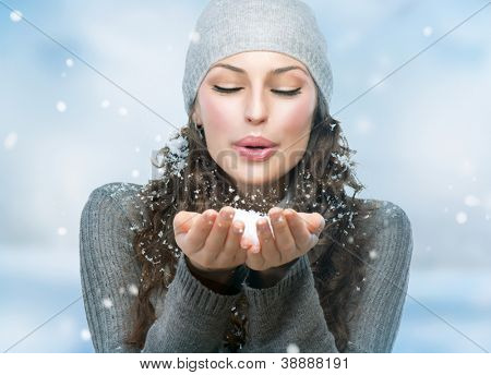 Christmas Girl.Winter woman Blowing Snow
