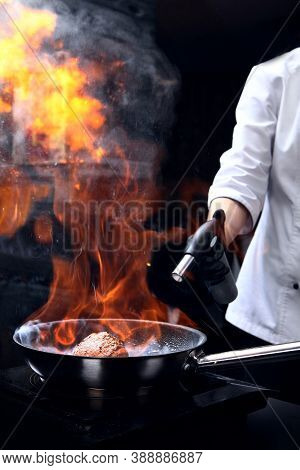 The Chef Uses A Gas Burner To Cook The Meat. Cooking A Piece Of Meat. Vertical Photo On A Black Back