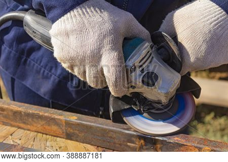 A Worker In Overalls Is Grinding A Weld Seam On A Steel Square Profile Pipe With An Angle Grinder Wi