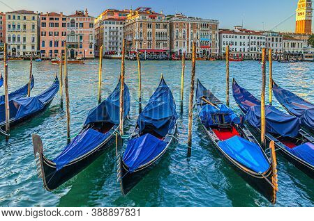 Gondolas Moored In Water Of Grand Canal Waterway In Venice. Baroque Style Colorful Buildings Along C