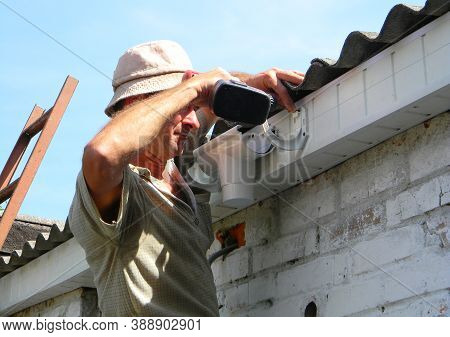 Kyiv, Ukraine - October  13, 2020:  Roof Guttering Installation: A Building Contractor Is Fixing A P