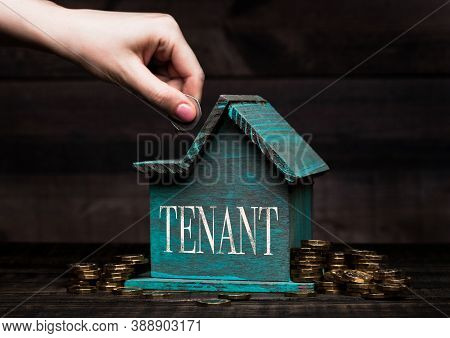 Wooden House Model With Coins Next To It And Hand Holding The Coin With Conceptual Text. Tenant