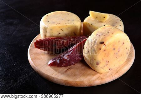 Large Chunks Or Heads Of Cheese On A Wooden Board. Dried Sausage In Large Chunks. Photo On A Black B