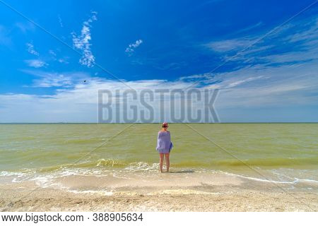 A Lonely Girl Stands In The Water On The Surf Line, Wrapped In A Towel. Summer Sunny Day At The Seas