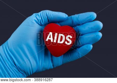 Doctor In Blue Gloves Holds A Heart With Text Aids Acquired Immune Deficiency Syndrome , Concept