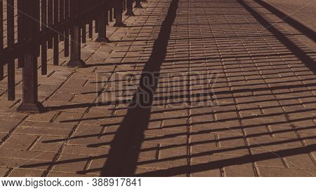 Shadow Of The Iron Fencing On The Pavement. Summer Day. Abstract Background