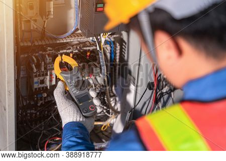 Digital Clamp Meter In Hands Of Electrician Close-up Against Background Of Electrical Wires And Rela