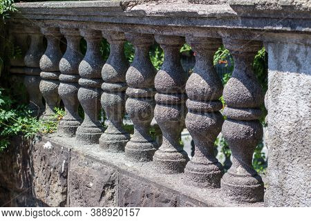 A Row Of Gray Stone Balusters. Part Of A Stone Fence In The Park With Green Vegetation
