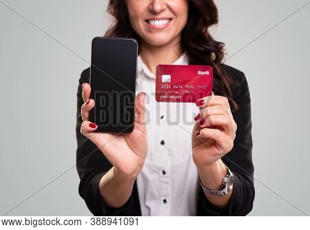 Crop Optimistic Business Lady Demonstrating Mobile Phone And Credit Card For Online Banking Service