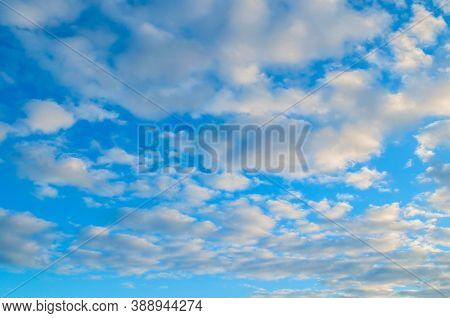 Blue dramatic sky background, white dramatic colorful clouds lit by sunlight. Blue sky background, vast sky landscape, sky scene with dramatic clouds.