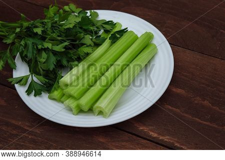 Green Sliced Celery Stalks And A Bunch Of Parsley On A White Plate Close-up And On A Brown Wooden Ba