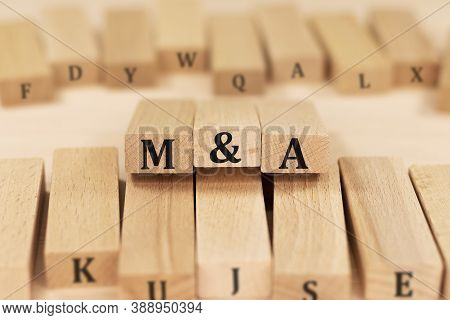 Word M And A Merger And Acquisition On Wooden Blocks Beige Background Top View, Scattered Cubes Arou