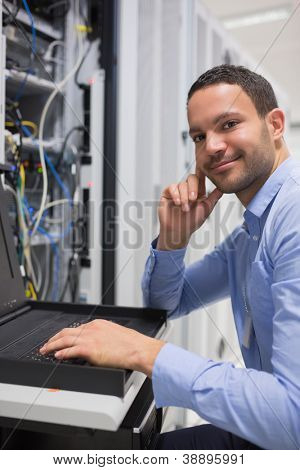 Happy man working with servers in data center
