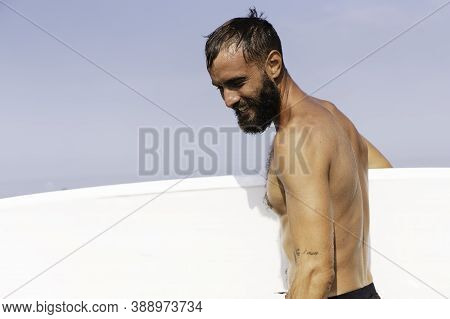 Young Smiling Surfer Holding His Surfboard On The Beach - Handsome Hipster Man Waiting Waves For Sur