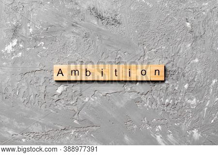 Ambition Word Written On Wood Block. Ambition Text On Cement Table For Your Desing, Concept