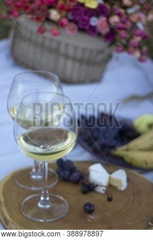 Wooden Stand With Two Glasses Of Champagne, Grapes And Camembert Cheese On A White Blanket In The Fi